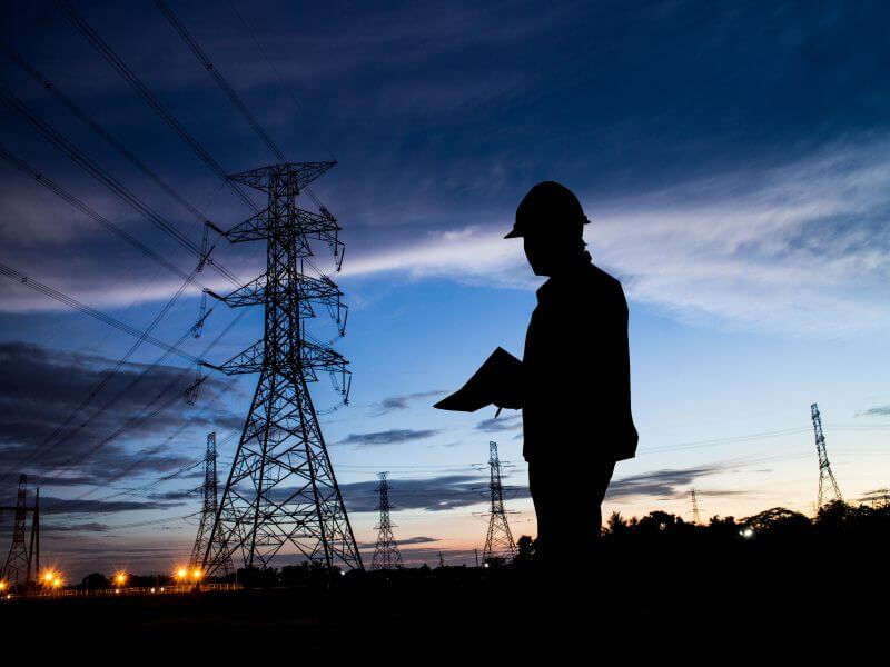 silhouette man of engineers standing at electricity station fieldpro